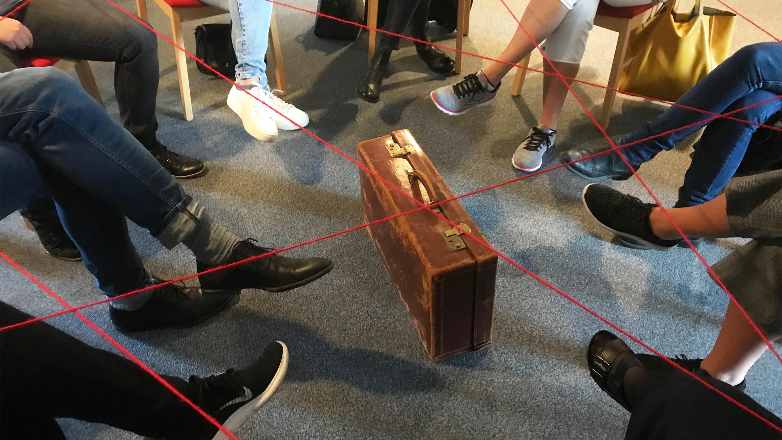 Personer sitter i en ring och håller upp en röd tråd som ett nätverk mellan sig