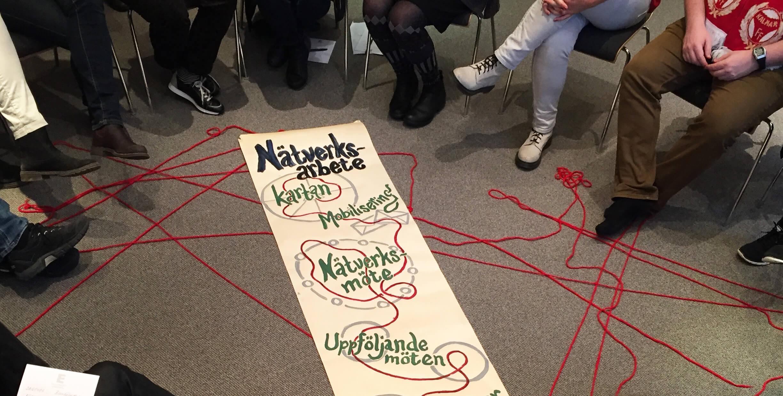Personer sitter i en ring runt ett paper som visar nätverksmötets röda tråd